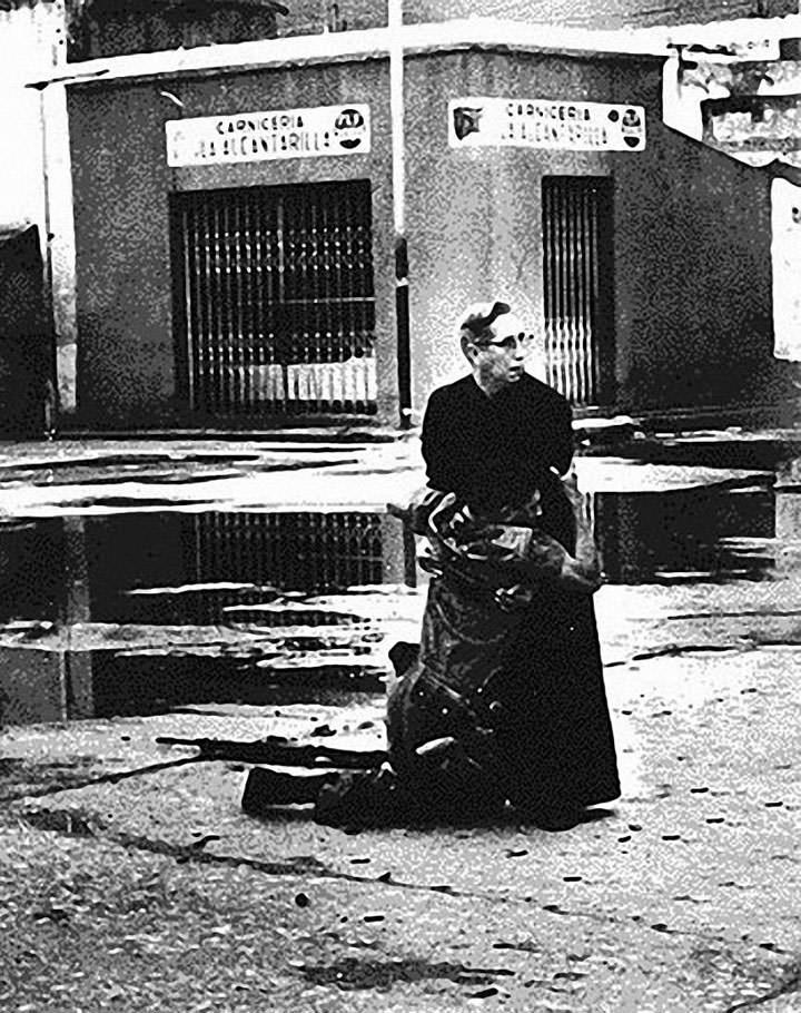 Le prêtre Luis Maria Padilla serrant dans ses bras un soldat blessé